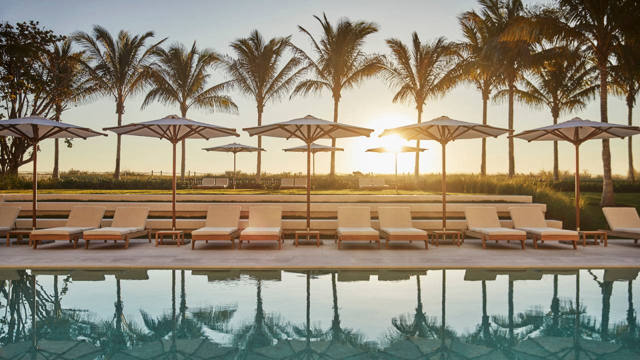sunset view of the pool lined with palm trees at Surf Club Four Seasons