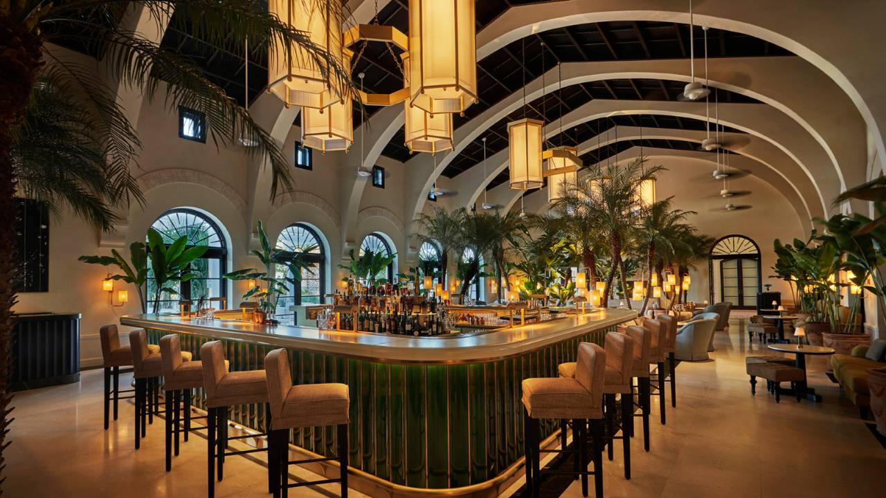 A view of The Surf Club Four Seasons' elegant Champagne Bar lined with bar stools and lantern mood lighting