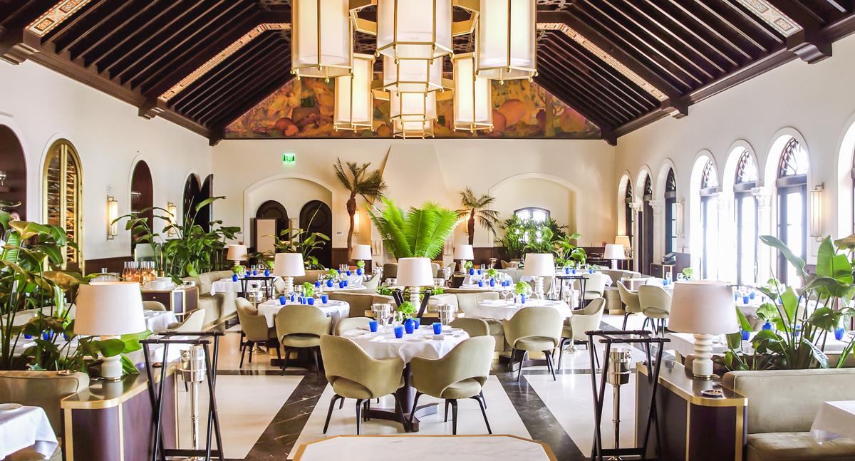 A large dining room at the Surf Club Four Seasons with white tablecloths, large brown modern chairs, lush green plants and open round windows
