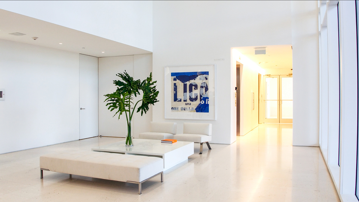 large open room inside condo at Surf Club Four Seasons with all white walls and large plant on a table and a modern painting