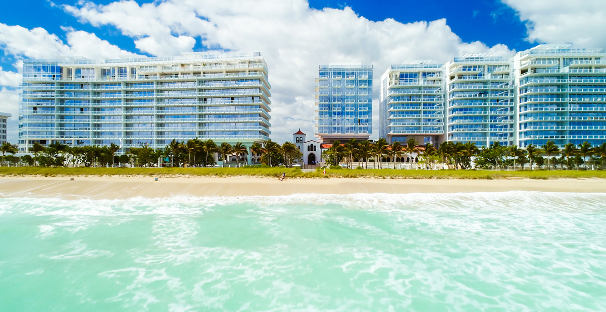 A view of the Surf Club Four Seasons towers from the Atlantic Ocean lined with palm trees.