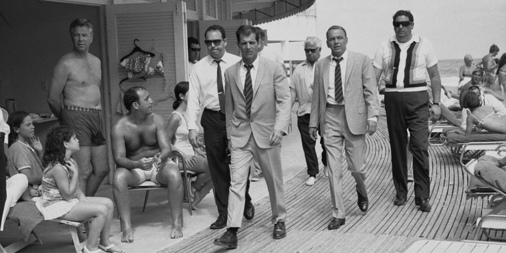 black and white historic photo of Frank Sinatra walking along the shores of the Surf Club with on-lookers