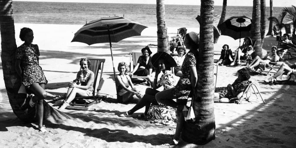 A historic black and white picture of day at the beach, cabana style, at the Surf Club.