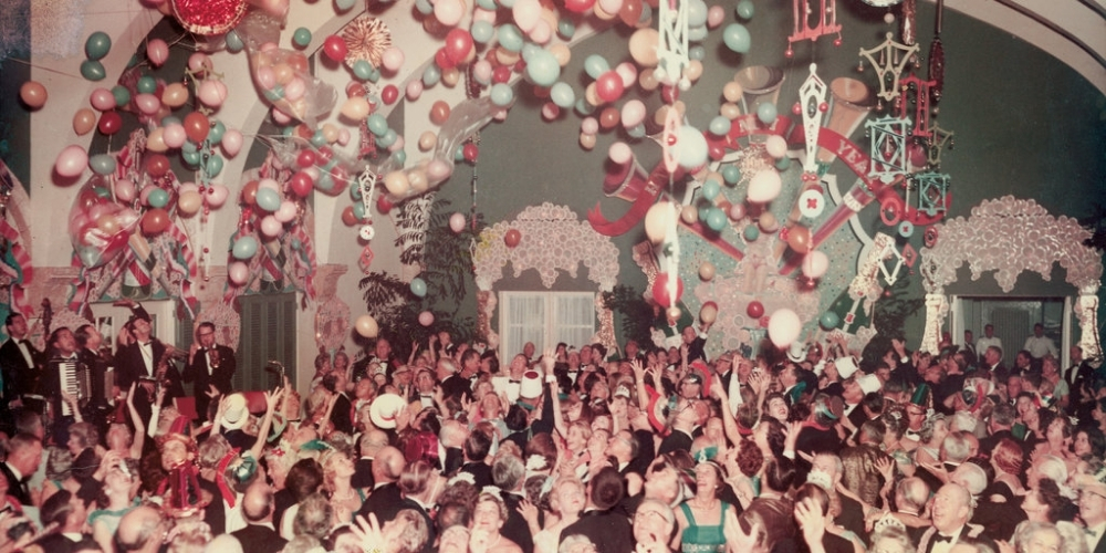 large New Years Eve party with many people dancing and celebrating in formal attire with balloons lining the ceiling at the Surf Club circa 1940's.