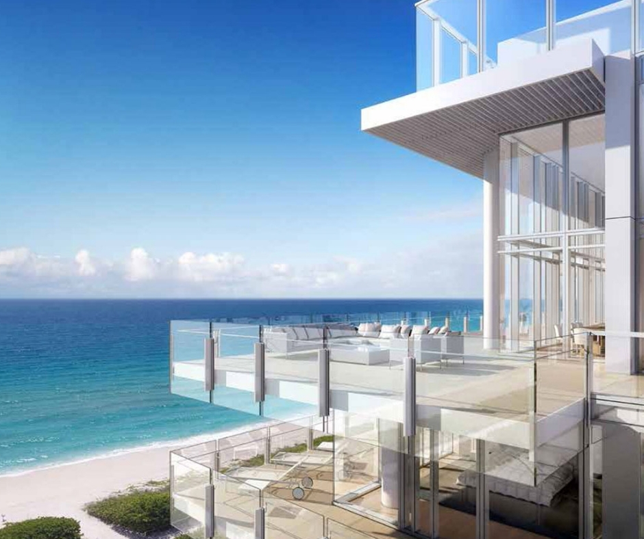 View of surf club condo with large outdoor patio with glass walls and railings with view of miami beach in the background