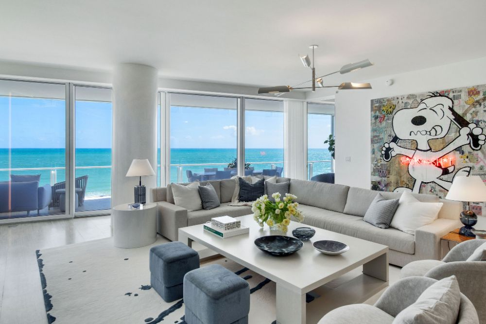 large living room in Surf Club condo with white coffee table, couches, and modern artwork