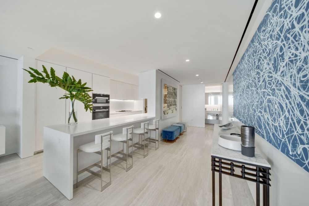 Wide hallway in condo of surf club with modern art and a bar length table with bar stools