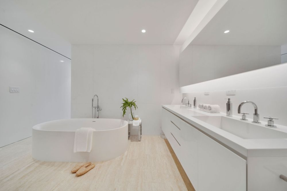 A stunning bathroom with white countertops and a large tube inside the residences at the Surf Club