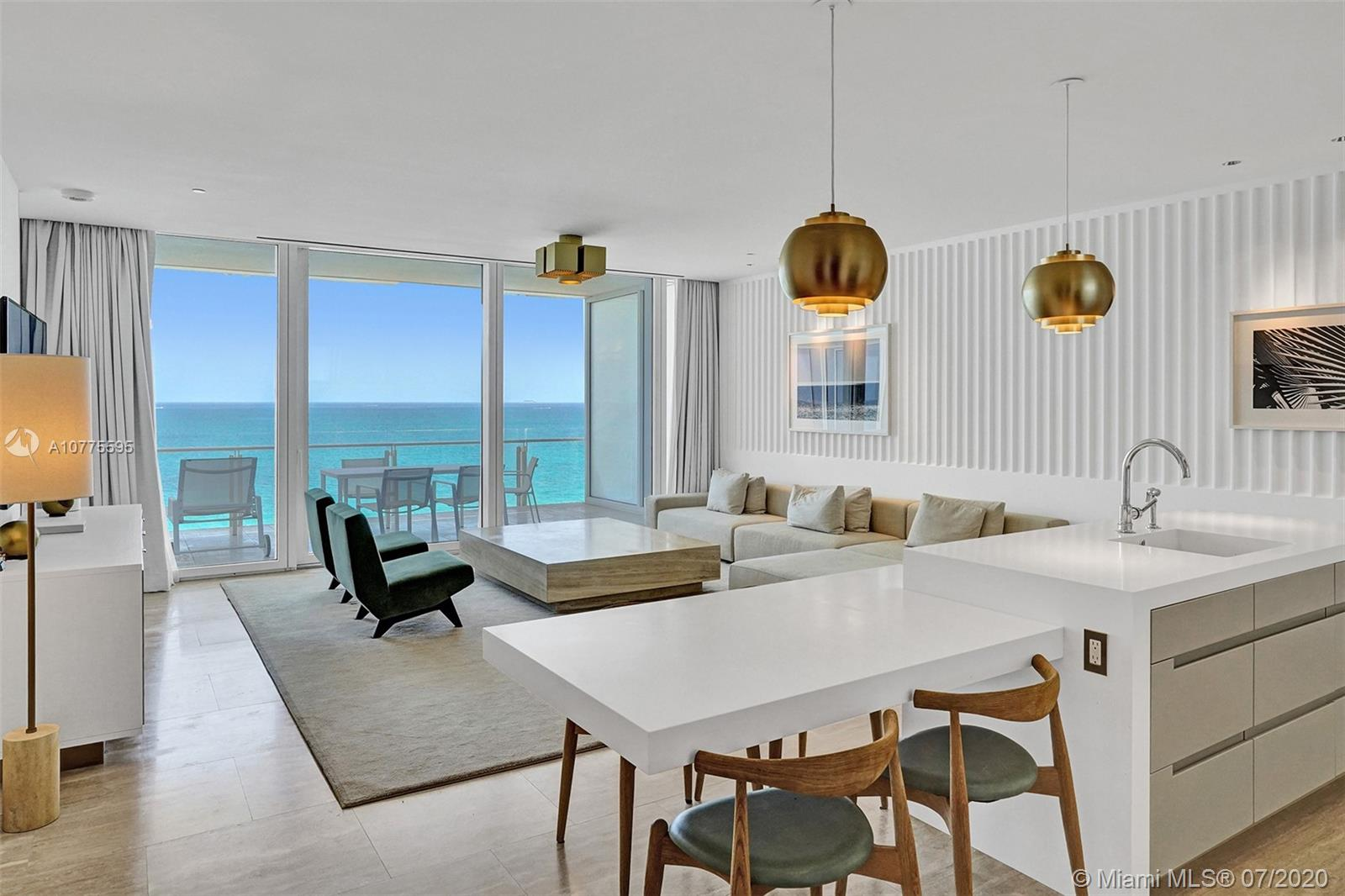 view from inside condo n-1013 at the surf club, room has a large marble coffee table, black modern chairs, white countertops with a view of miami beach.