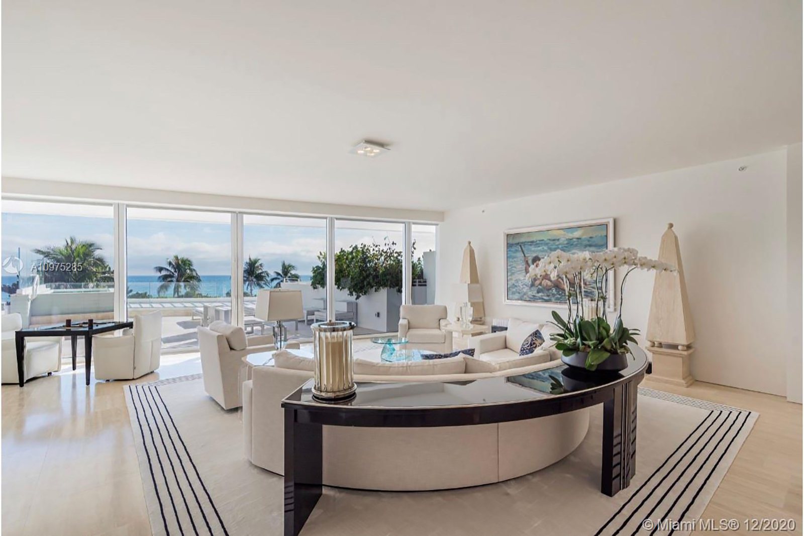 view from within s-205 featuring an open floor plan with white furniture and black tables and orchids over with a view of palm trees and Miami beach.